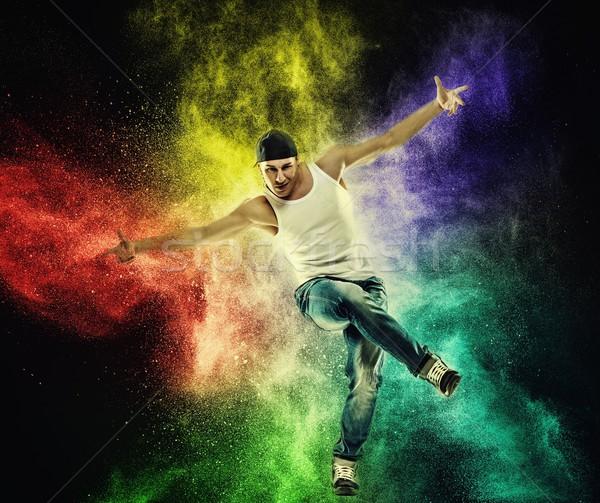 Man dancer showing break-dancing moves against colourful powder explosion Stock photo © Nejron