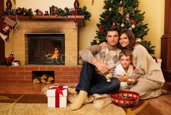 Family near fireplace in Christmas decorated house interior with gift box Stock photo © Nejron