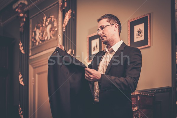 Middle-aged man looking at suit on a hanger  Stock photo © Nejron