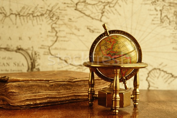 Globe and vintage book against map on a wall. Stock photo © Nejron