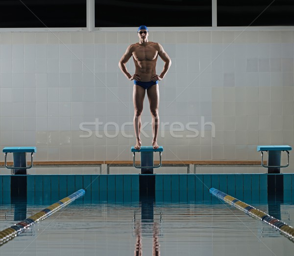 Young muscular swimmer standing on starting block in a swimming pool Stock photo © Nejron