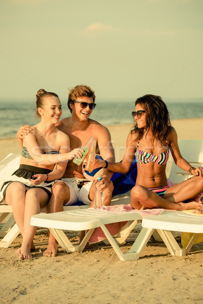 Group of multi ethnic friends sunbathing on a deck chairs on a beach  Stock photo © Nejron