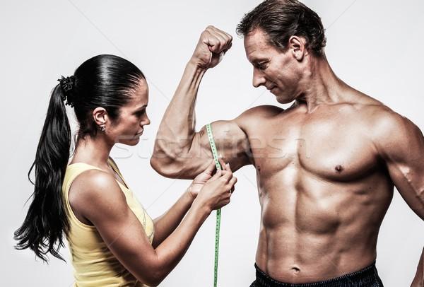 Woman measuring athletic's man biceps Stock photo © Nejron