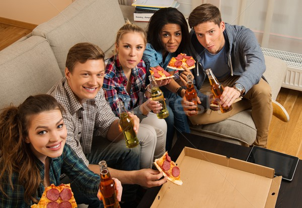 Group of multi-ethnic friends with pizza and bottles of drinks having party Stock photo © Nejron