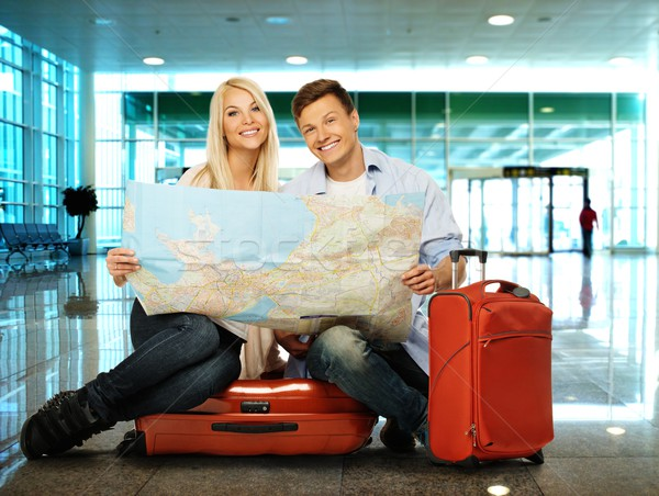 Young couple with map sitting on suitcases in airport Stock photo © Nejron