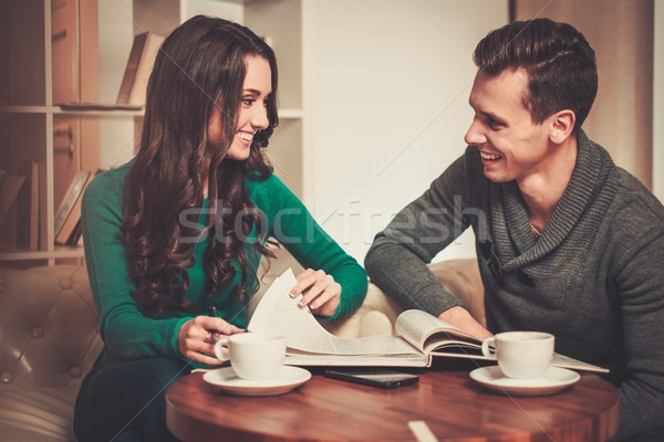Couple with coffee and book discussing something in cafe  Stock photo © Nejron