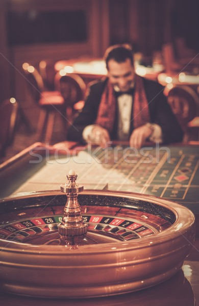 Man in suit and scarf playing roulette in a casino Stock photo © Nejron
