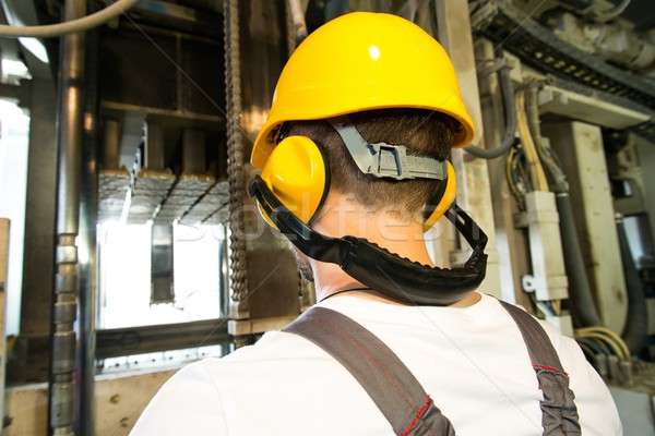 Worker in safety hat and headphones working behind machine on a factory Stock photo © Nejron