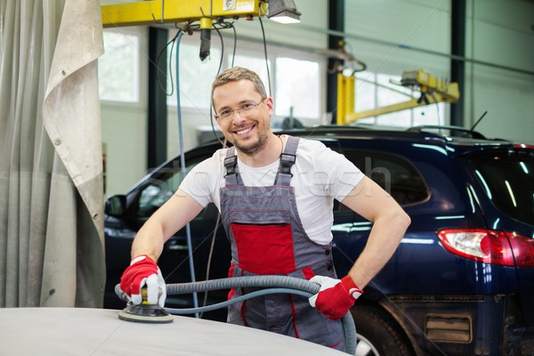 Cheerful serviceman performing grinding with machine on a car bonnet in a workshop Stock photo © Nejron