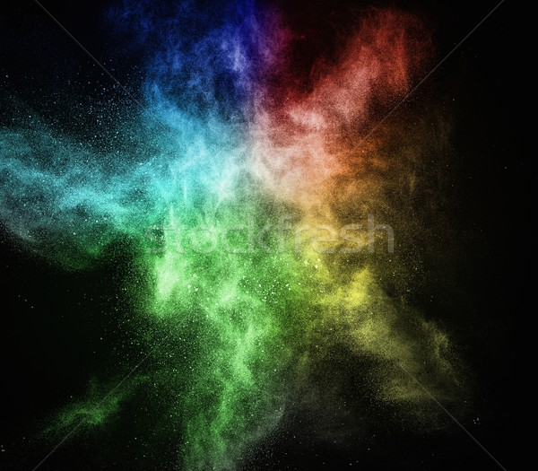 Stock photo: Colourful powder exploding isolated on black
