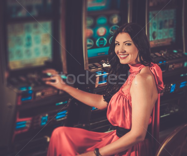 Stock photo: Beautiful woman in red dress playing slot machine