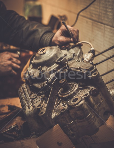 Mechanic working with with motorcycle engine in a workshop Stock photo © Nejron