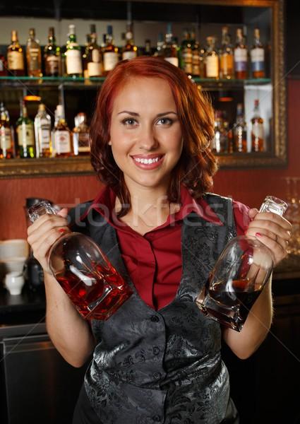 Beautiful redhead barmaid with bottles behind bar counter  Stock photo © Nejron