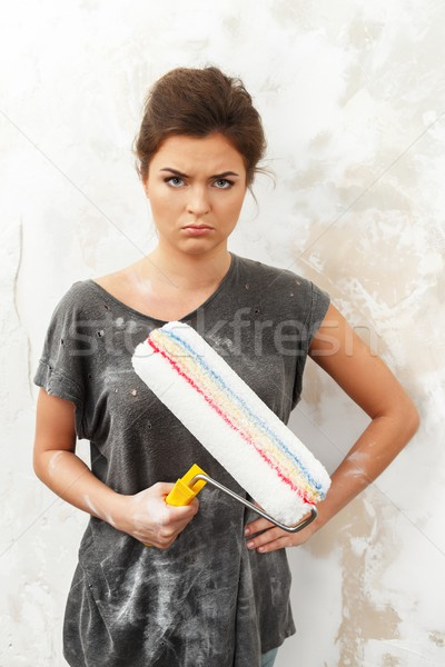Disgruntled young brunette woman doing wall painting   Stock photo © Nejron