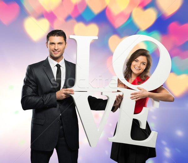 Beautiful smiling couple holding word LOVE over bokeh background  Stock photo © Nejron