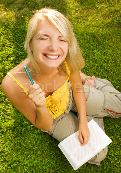 Funny wide angle portrait of a young woman reading book outdoors Stock photo © Nejron