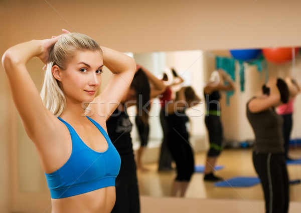 Beautiful young woman doing fitness exercise in a sport club Stock photo © Nejron