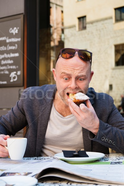 Surprised middle-aged man reading newspaper behind table in street cafe during coffee pause Stock photo © Nejron