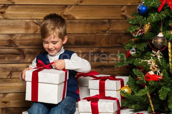 Kicsi fiú nyitás ajándék doboz karácsonyfa fából készült Stock fotó © Nejron