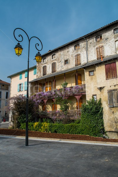 Streetlight in front of building facade with balconies full of flowers in Saint-Girons town, France  Stock photo © Nejron