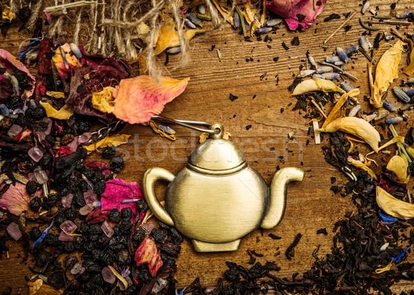 Teapot trinket among flower tea petals on wooden table background Stock photo © Nejron