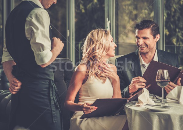 Cheerful couple with menu in a restaurant making order Stock photo © Nejron
