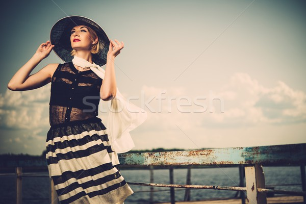 Woman in white hat and scarf standing near old pier rails  Stock photo © Nejron