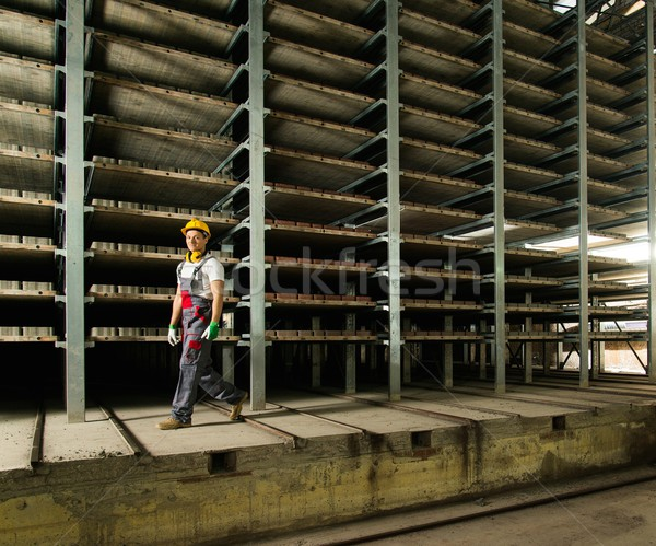 Worker in safety hat walking in a storage room on a factory Stock photo © Nejron