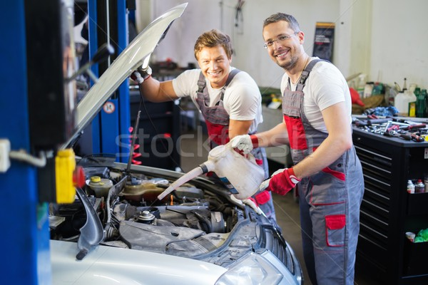 Two mechanics adding oil level in a car workshop Stock photo © Nejron