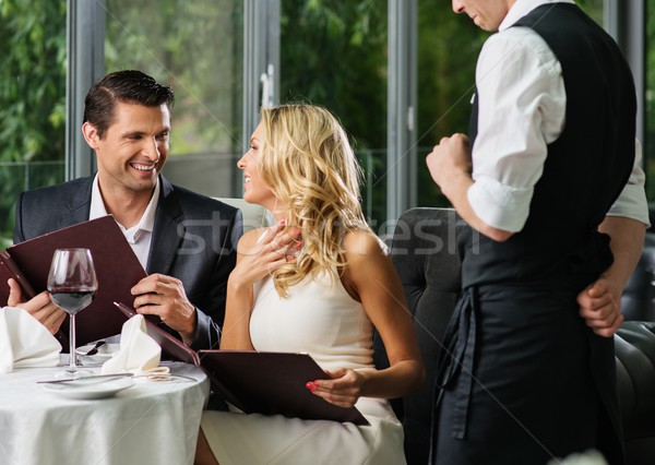 Cheerful couple with menu in a restaurant  Stock photo © Nejron