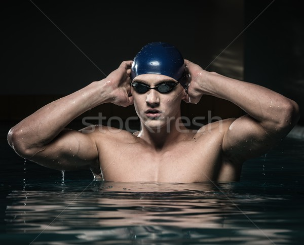 Muscular young man in blue cap in swimming pool Stock photo © Nejron