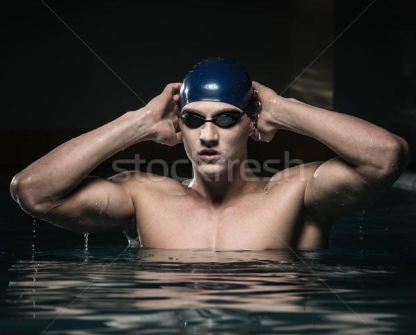 Muskularny młody człowiek niebieski cap basen wody Zdjęcia stock © Nejron