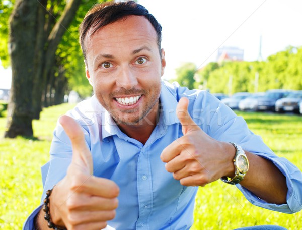 Happy handsome middle-aged man showing thumbs up outdoors  Stock photo © Nejron