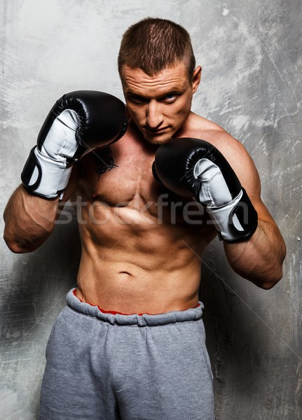 Young sporty man in boxing gloves posing  Stock photo © Nejron