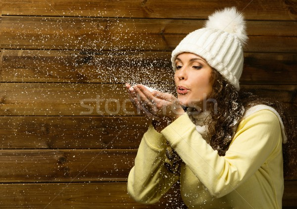 Beautiful woman in knit hat blowing snow from her hands Stock photo © Nejron