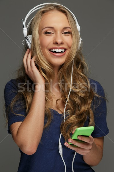 Positive young woman with long hair and blue eyes listens to music Stock photo © Nejron