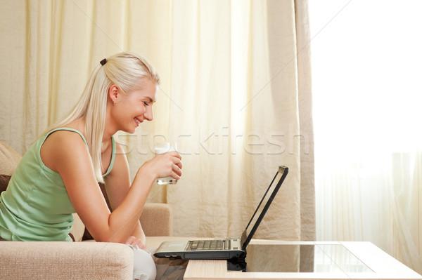 Foto d'archivio: Bella · donna · bere · latte · utilizzando · il · computer · portatile · donna · casa