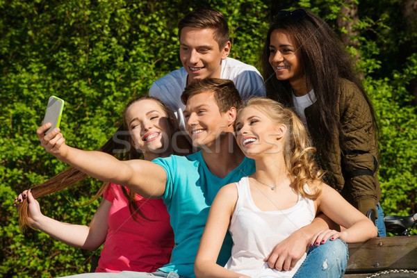 Multi ethnic group of sporty teenage friends in a park taking selfie Stock photo © Nejron
