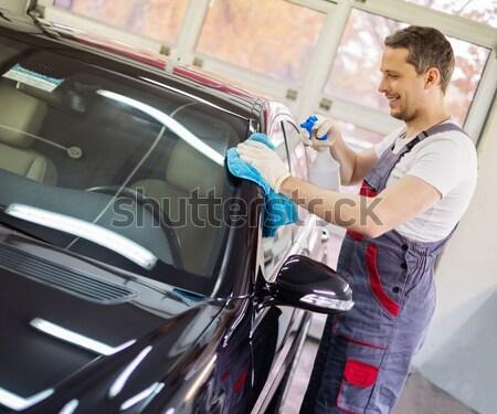 Cheerful serviceman unscrewing wheel in car workshop  Stock photo © Nejron