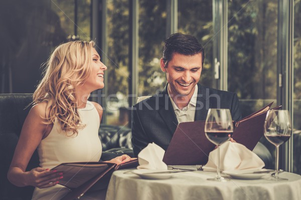 Stock photo: Cheerful couple with menu in a restaurant