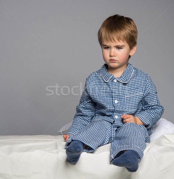 Disappointed little boy in blue pyjamas on bed Stock photo © Nejron
