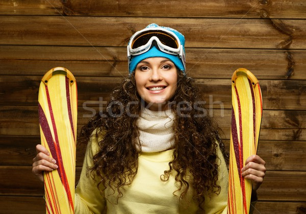 Smiling woman with skies standing against wooden house wall  Stock photo © Nejron