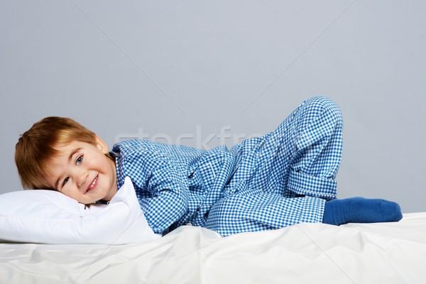 Little boy wearing blue pyjamas in bed Stock photo © Nejron