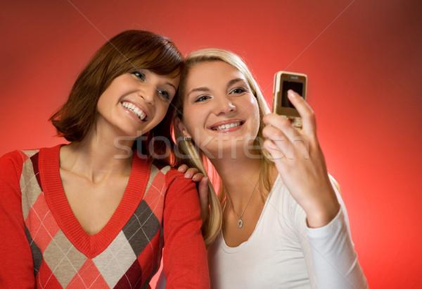 Two beautiful girls making self-portrait using mobile phone Stock photo © Nejron