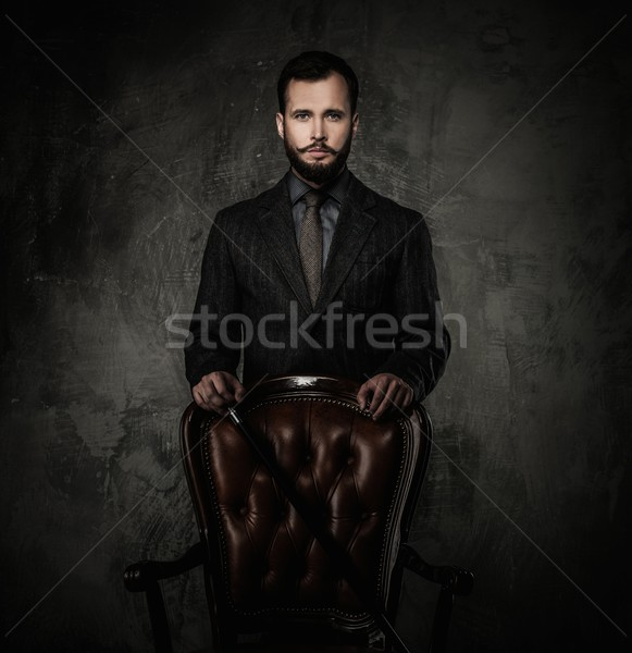 Handsome well-dressed man with walking stick standing near leather chair  Stock photo © Nejron