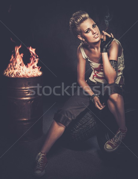 Punk girl smoking a cigarette sitting on a tires  Stock photo © Nejron