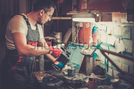 Stock photo: Serviceman cleaning airbrush gun in a car body workshop