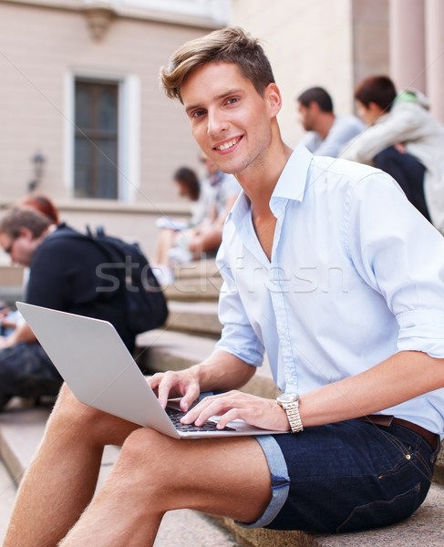 Handsome young man with laptop sitting on a steps outdoors Stock photo © Nejron