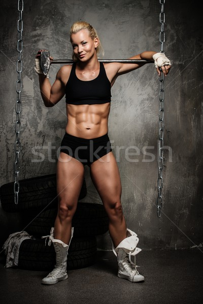 Stock photo: Beautiful muscular bodybuilder woman standing near stack of  tyres with hammer on her shoulders