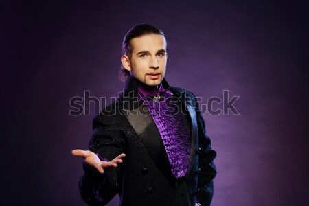 Young handsome brunette magician in stage costume  Stock photo © Nejron